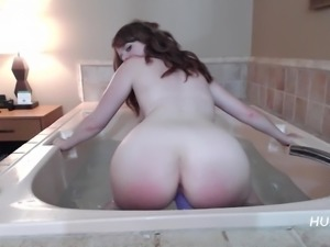 Redhead Riding dildo in jetted tub