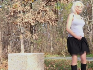 Busty and curvaceous blondie in the park pisses behind the concrete