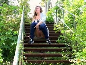 Cute amateur college girl in the park pulls down her jeans