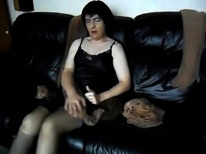 Alluring crossdresser in stockings masturbates on the sofa