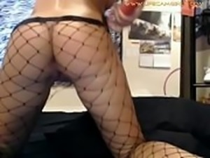 Punk girl in net pantyhose pushes dildo in her pussy and shows closeup