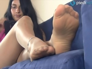 An amateur girl showing her feet and anklet on the couch