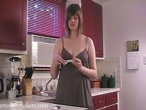 Kinky brown-haired milf smokes and shows her tits in the kitchen